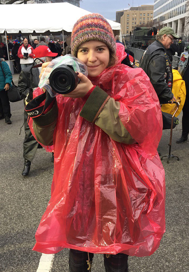Student Robi Foli is poised with a camera in DC.